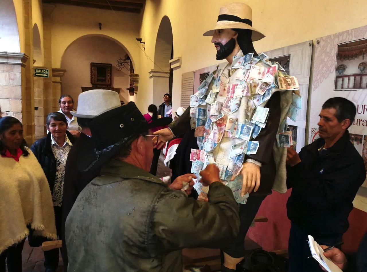 Cuatro de los priostos fueron los encargados de retirar uno a uno los billetes de 2.000, 5.000, 10.000, 20.000 y 50.000 pesos que momentos antes habían sido prendidos con un alfiler por los devotos a la ruana